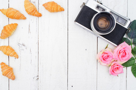 Vintage Camera, Instax Photos and Croissant on White Wooden Background, Flat Lay Style with Free Text Space