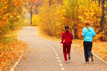 fall scenery: Two young girls run in the park. Stock Photo