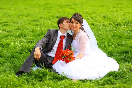 Groom and bride sitting on the green grass. photo