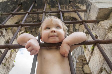 behind bars: The girl child behind bars Stock Photo
