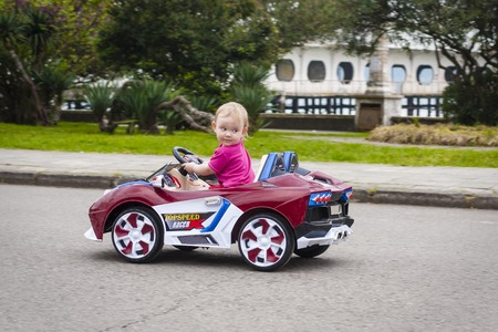 Baby girl riding on a small car Stock fotó