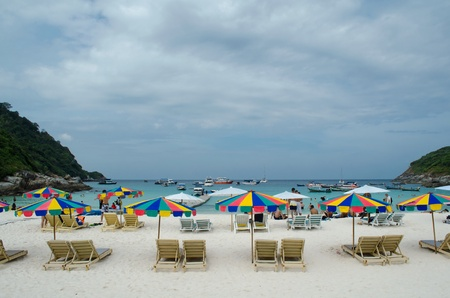 sun bath chairs and colorful parasol at Raya island in Phuket