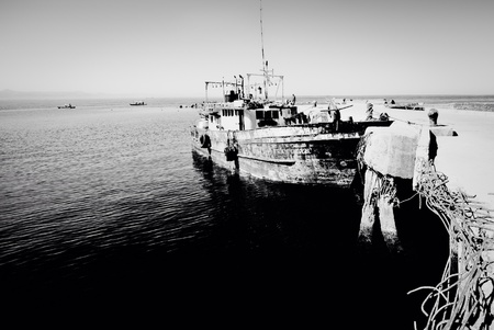 fishingboat: Old fishing boat at the pier in black and white. Stock Photo