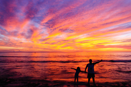 Father and daughter enjoying the sunrise at the beach at Pagudpud Ilocos Norte.
