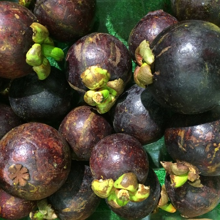superfruit: Bunch of mangosteen for sale at the grocery.