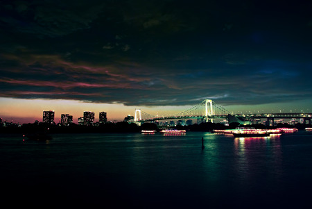 urbanscape: After sunset at Tokyo viewed from Odaiba. The city is covered with dark clouds. Rainbow Bridge is at the background Stock Photo