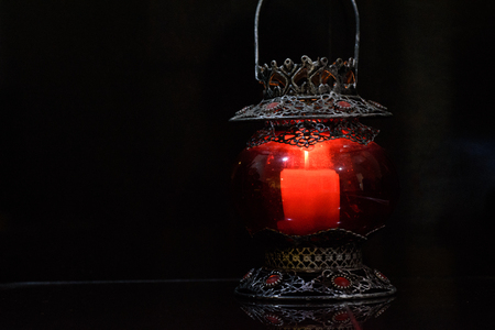 candle holder: Red candle holder in black background. Stock Photo
