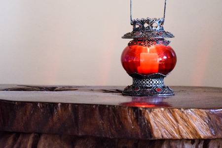 candle holder: Red candle holder at the wooden table. Stock Photo