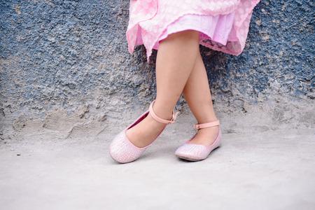 feet crossed: Little girl in crossed feet in lovely shoes.