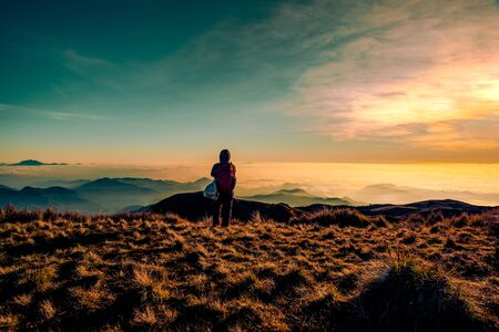 An adult mountainer standing at the peak of Mt. Pulag enjoying the breathtaking view of sea of clouds during sunrise.