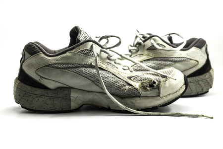 Worn old running shoes on white background
