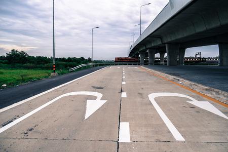 cul de sac: A U turn arrow traffic symbol under the elevated highway