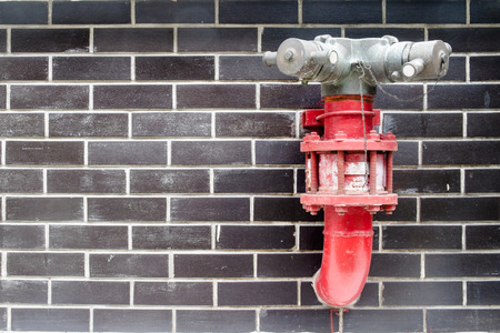 fire brick: Red fire hydrant in the black brick wall Stock Photo