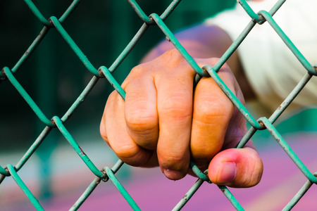 imprisonment: hand on the chain-link fence,concept of life imprisonment