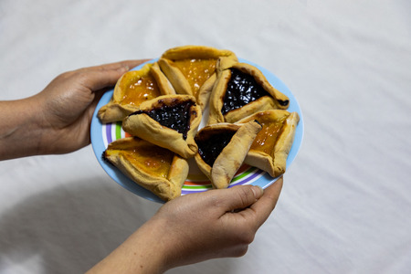 woman hands holding a colored plate with Hamantash Purim Blueberry and apricot jam cookies on white tablecloth Standard-Bild