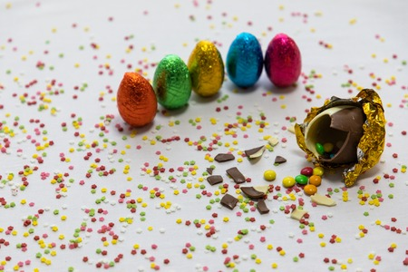 Broken golden chocolate easter eggs with colorful chocolates inside on white background with colorful blurred confetti and other colored eggs