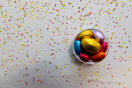 Colorful chocolate easter eggs in a transparent bowl with white background and blurred confetti