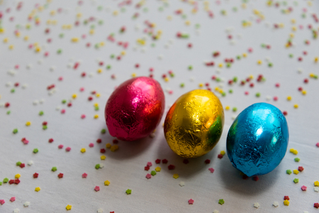 Three colored chocolate easter eggs on white background and colorful confetti
