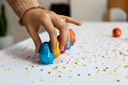 Woman hand setting up colorful chocolate easter eggs