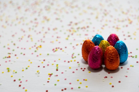 Many standing colored chocolate easter eggs on white background and colorful confetti Stockfoto