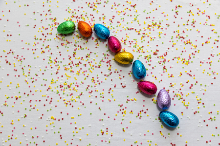 Many aligned colored chocolate easter eggs on white background and colorful confetti