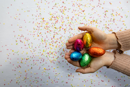 Woman hands holding colorful chocolate easter eggs with white background and colorful blurred confetti