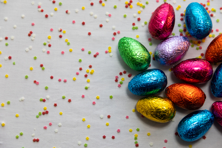 Many colored chocolate easter eggs on white background and colorful confetti Stockfoto