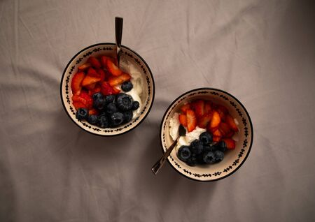 Top view of two bowls with yogurt, strawberries and blueberries over grey sheets