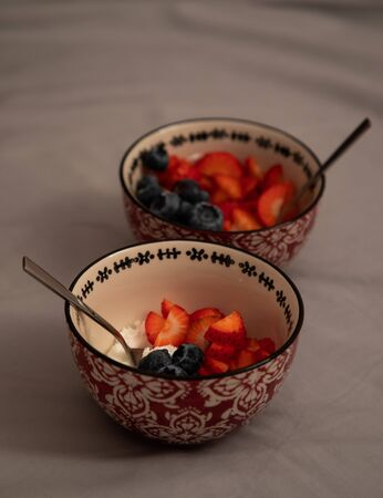 Top side view of two bowls with yogurt, strawberries and blueberries over grey sheets