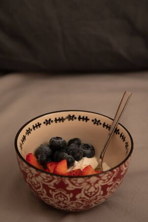 Top side view of a bowl with yogurt, strawberries and blueberries over grey sheets