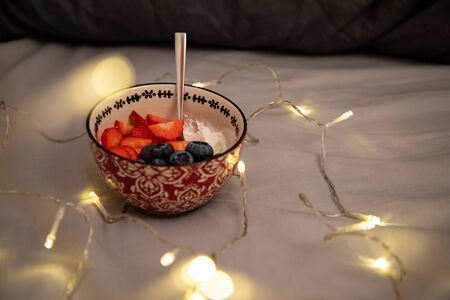 Top side view of a bowl with yogurt, strawberries and blueberries over grey sheets with lights