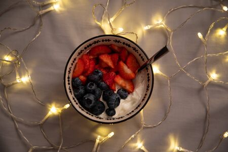 Top view of a bowl with yogurt, strawberries and blueberries over grey sheets with lights