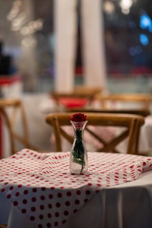Close up of the centerpiece of a spanish restaurant table with red checkered tablecloth and wood chairs