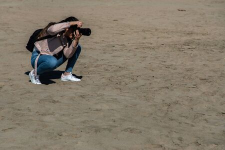 Woman crouching taking a picture with a DSLR camera on the beach Stock Photo