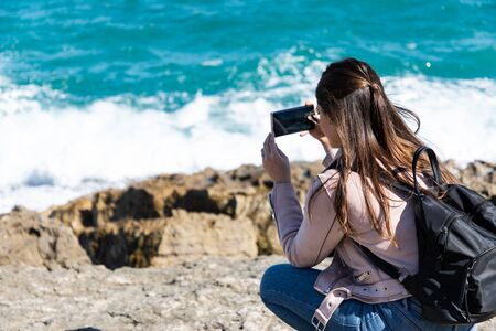 Woman crouching taking pictures of shore with smart phone