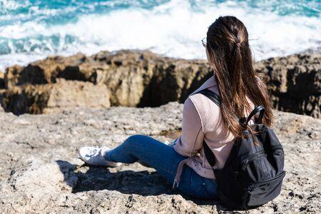 Beautiful woman sitting on the shore watching the waves 版權商用圖片