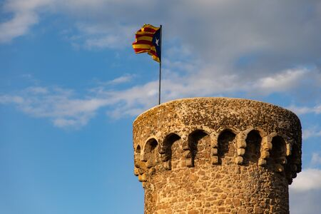 Independentist flag waving on top of medieval tower cloudy sky