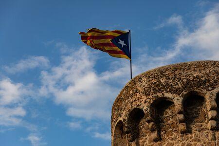 Bandera independentista ondeando en la parte superior de la torre medieval cielo nublado Foto de archivo