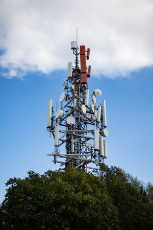 Cell antenna over the tree with cloudy sky