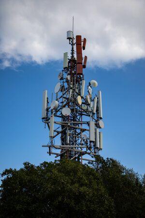 Antenne cellulaire au-dessus de l'arbre avec ciel nuageux Banque d'images