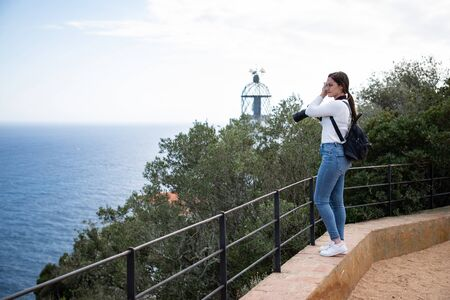 Woman taking picture of beach from high point with blurred lighthouse on the background