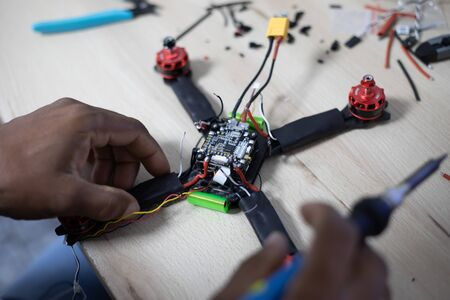 Black man mounting and soldering racing drone on wooden table