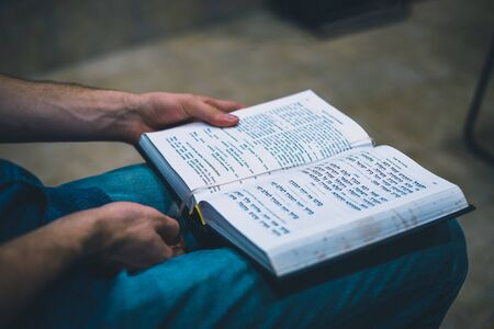 Sited man studying the torah on hes knees unrecognizable Stock fotó