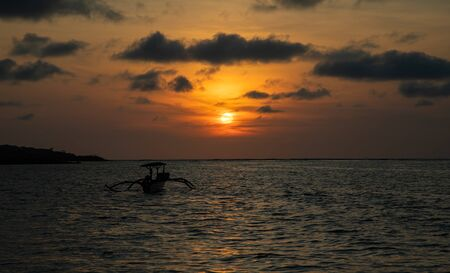 Sunset over calm ocean with balinese boat