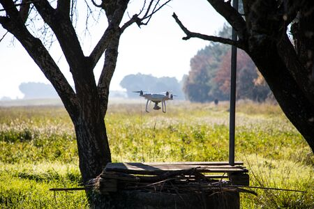 Drone over water well and under tree on sunny winter morning