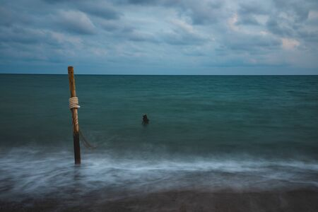 Long exposure of sea water with wooden logs and rope, on cloudy sky Фото со стока