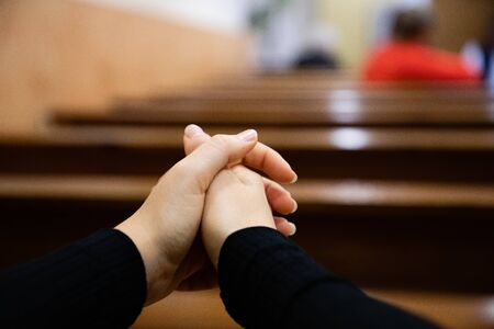 Close up of a woman hands praying at the church