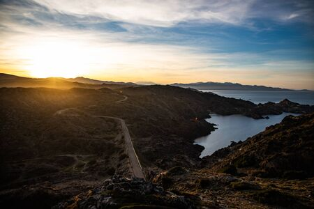View of a mountain curved road with sunset sky in Cap de Creus, Catalunya