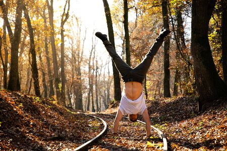 Man doing handstand on train rails with leaves on the ground during sunset