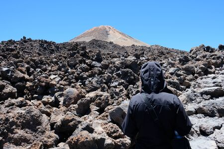 Woman ascending the Teide mountain peak on a dry and rocky volcanic landscape with copy space